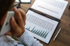 A mulher de negócio no local de trabalho na tabela de madeira do escritório analisa os dados, programações, fixa o preço, faz de  foto de stock