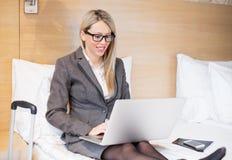 Mulher de negócio no terno que senta-se na cama e que trabalha com o computador na sala de hotel fotos de stock