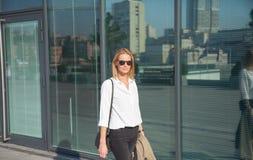 Mulher de negócio nos óculos de sol que anda no revestimento de trincheira da terra arrendada da rua fotografia de stock