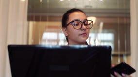Mulher de negócio nos vidros com o cabelo escuro que corre usando o computador e o telefone celular que sentam-se na tabela no es video estoque