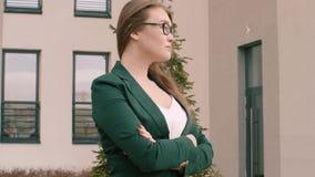Mulher de negócio nos vidros e no terno de negócio exteriores, fundo do escritório para negócios filme