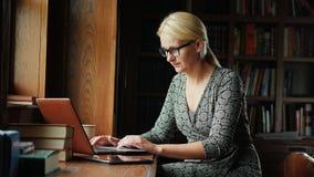A mulher de negócio nos vidros trabalha com um portátil em uma biblioteca ou em um escritório luxuoso No fundo, prateleiras com l filme