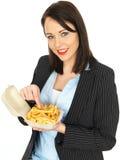 Mulher de negócio nova atrativa feliz que come microplaquetas Fotografia de Stock