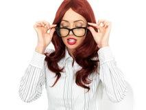 Mulher de negócio nova atrativa que espreita sobre seus vidros Imagens de Stock Royalty Free
