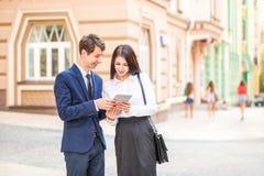 A mulher de negócio nova bonita e o homem de negócios considerável em ternos formais estão usando uma tabuleta digital no fundo d Fotografia de Stock