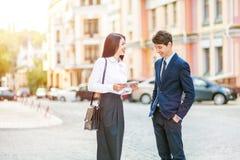 A mulher de negócio nova bonita e o homem de negócios considerável em ternos formais estão usando uma tabuleta digital no fundo d Foto de Stock