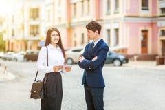 A mulher de negócio nova bonita e o homem de negócios considerável em ternos formais estão usando uma tabuleta digital no fundo d Imagens de Stock