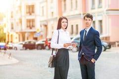 A mulher de negócio nova bonita e o homem de negócios considerável em ternos formais estão usando uma tabuleta digital no fundo d Imagens de Stock Royalty Free