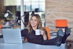 Mulher de negócio nova bonita feliz que senta-se e que fala no telefone celular no escritório Fotografia de Stock