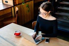 A mulher de negócio nova bonita nos vidros que sentam-se na cafetaria, trabalha em um portátil foto de stock royalty free