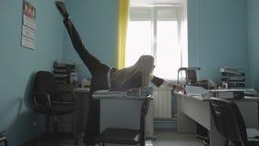 Mulher de negócio nova bonita que faz o exercício ginástico no vídeo da metragem do estoque do escritório vídeos de arquivo