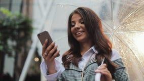 Mulher de negócio nova bonita que usa o smartphone na rua no tempo chuvoso, sorrindo, guarda-chuva da terra arrendada, uma comuni filme