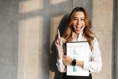 Mulher de negócio nova bonita vestida na camisa formal da roupa que guarda dentro apontar dos documentos fotografia de stock