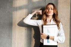 Mulher de negócio nova bonita vestida na camisa formal da roupa que guarda dentro os documentos que mostram os bíceps imagem de stock