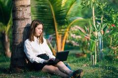 Mulher de negócio nova com o caderno que senta-se no parque fotografia de stock