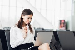 Mulher de negócio nova com portátil e o petisco saudável em sua mão que senta-se na porta terminal das partidas O viajante espera fotos de stock