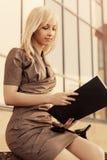 Mulher de negócio nova da forma com a pasta de arquivos no prédio de escritórios imagem de stock royalty free