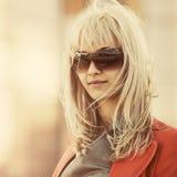 Mulher de negócio nova da forma nos óculos de sol que anda na rua da cidade foto de stock