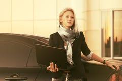 Mulher de negócio nova da forma que usa o portátil ao lado de seu carro imagem de stock