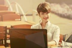 Mulher de negócio nova da forma que usa o portátil no café do passeio imagem de stock royalty free