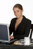 Mulher de negócio nova de sorriso no computador Fotografia de Stock Royalty Free