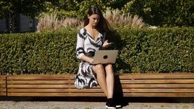 Mulher de negócio nova em um vestido que senta-se em um banco com um telefone à disposição e um computador filme