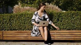 Mulher de negócio nova em um vestido que senta-se em um banco com um telefone à disposição e um computador video estoque