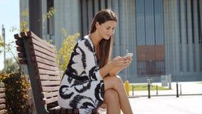 Mulher de negócio nova em um vestido que senta-se em um banco com um telefone à disposição e trabalhos video estoque
