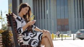 Mulher de negócio nova em um vestido que senta-se em um banco com um telefone à disposição e trabalhos vídeos de arquivo