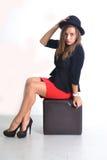 Mulher de negócio nova em uma saia vermelha e em um revestimento preto Fotografia de Stock Royalty Free