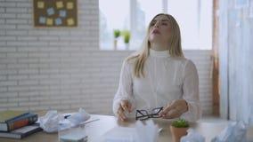 Mulher de negócio nova esgotada que decola seus vidros após o trabalho longo com o laptop no escritório Sentimento da mulher video estoque