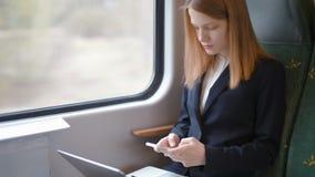 A mulher de negócio nova está trabalhando no portátil e está texting no telefone no trem vídeos de arquivo