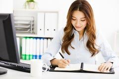 Mulher de negócio nova feliz que trabalha no escritório Foto de Stock