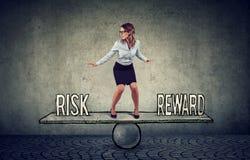 Mulher de negócio nova hábil que equilibra entre a recompensa e o risco imagens de stock royalty free