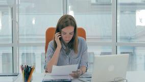Mulher de negócio nova na mesa com telefone e computador no escritório moderno filme
