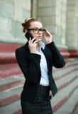 Mulher de negócio nova no terno preto e vidros que falam no telefone foto de stock