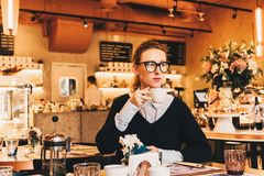 A mulher de negócio nova nos vidros senta-se em um café em uma tabela, bebe o café, guarda o smartphone em sua mão Foto de Stock