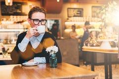 A mulher de negócio nova nos vidros senta-se em um café em uma tabela, bebe o café, guarda o smartphone em sua mão Fotografia de Stock
