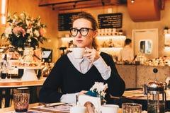 A mulher de negócio nova nos vidros senta-se em um café em uma tabela, bebe o café, guarda o smartphone em sua mão Foto de Stock Royalty Free