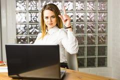Mulher de negócio nova que aponta acima com ideia na mesa no escritório Foto de Stock