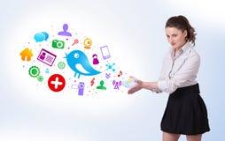 Mulher de negócio nova que apresenta ícones sociais coloridos ilustração stock