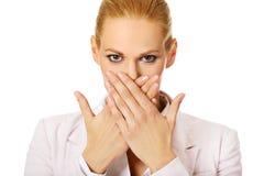 Mulher de negócio nova que cobre sua boca com as duas mãos Fotos de Stock