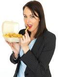 Mulher de negócio nova que come microplaquetas Fotografia de Stock Royalty Free