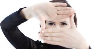 Mulher de negócio nova que faz uma moldura para retrato de suas mãos Fotografia de Stock Royalty Free
