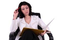 Mulher de negócio nova que lê um relatório Imagens de Stock Royalty Free