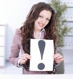 Mulher de negócio nova que mostra o cartaz com um ponto de exclamação fotografia de stock royalty free
