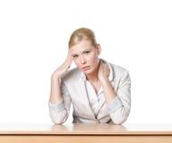 Mulher de negócio nova que senta-se em uma mesa de escritório fotografia de stock