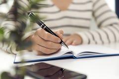 Mulher de negócio nova que senta-se na tabela e que escreve no caderno O foto de stock