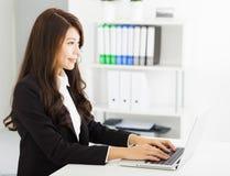 Mulher de negócio nova que trabalha com portátil Imagem de Stock Royalty Free