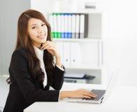 Mulher de negócio nova que trabalha com portátil Fotografia de Stock Royalty Free